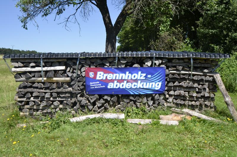 Stapel mit Brennholzabdeckung und Banner